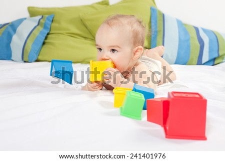 Baby girl playing with cube toys - stock photo