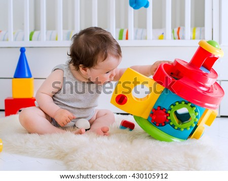 baby girl playing with educational toy in nursery - stock photo