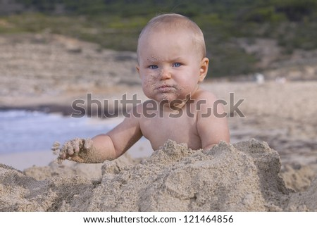 baby girl playing with sand on the beach - stock photo