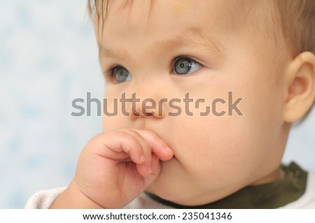 Baby girl portrait looking away with fingers in mouth