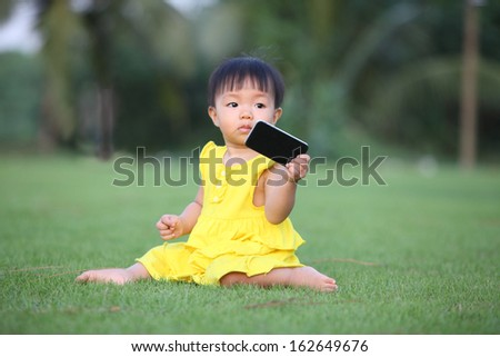 baby girl show her smartphone and sit on lawn - stock photo