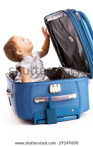 Baby girl sits inside the suitcase - stock photo