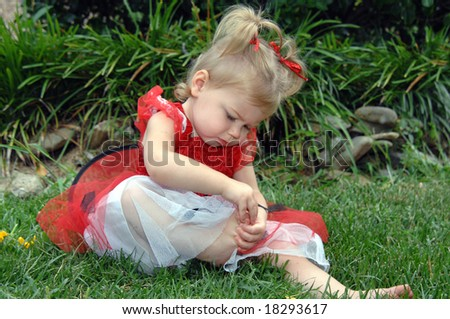 Baby girl sits on grass and examines her toes.  She has on a lady bug  costume with black dots, red frilly net, wings and is wearing red hair bows. - stock photo