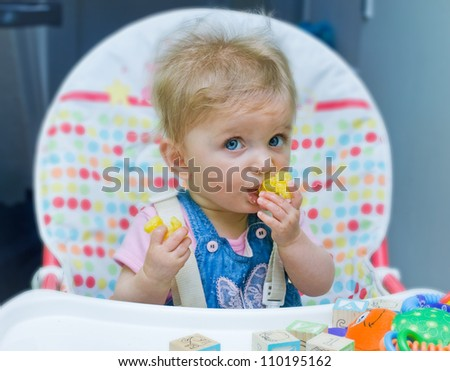Baby girl sitting in a highchair and feeding herself. - stock photo