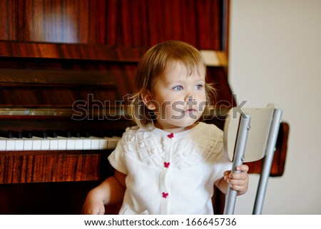 baby girl sitting next to the piano - stock photo