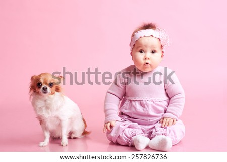 Baby girl sitting on floor with little dog over pink. Wearing stylish clothes. Looking at camera. Childhood. - stock photo