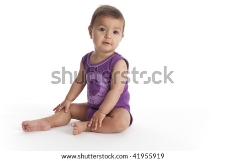 Baby girl sitting on the floor on white background - stock photo