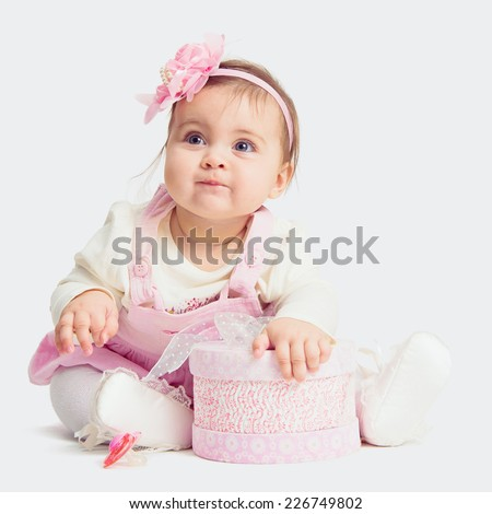 baby girl sitting on the floor with gift box  and looking up - stock photo