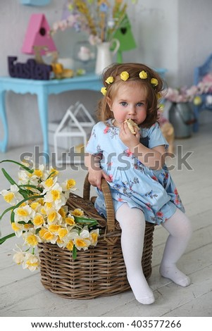 Baby girl sitting on the wooden basket with flowers, eating the easter bred - stock photo