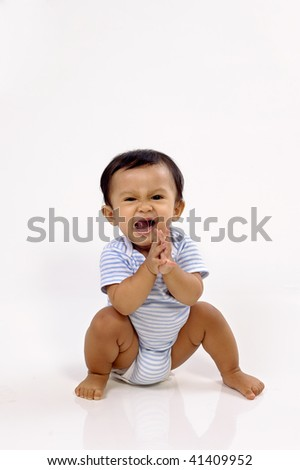 Baby girl sitting on white background, she clapping her hand - stock photo