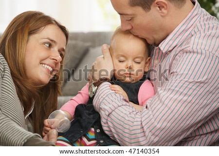 Baby girl sleeping in father's arm on sofa, father kissing on head, mother looking tenderly.