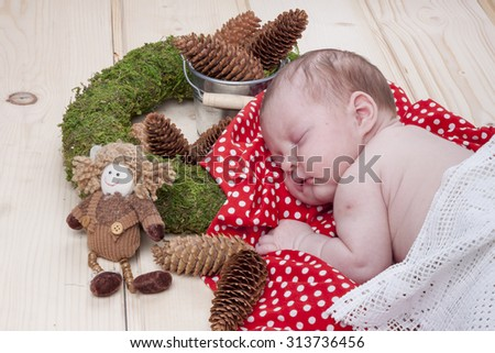 Baby girl sleeping on a red and white blanket - stock photo