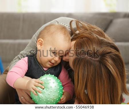 Baby girl smiling holding ball in hands, mum cuddling kissing baby on cheek.