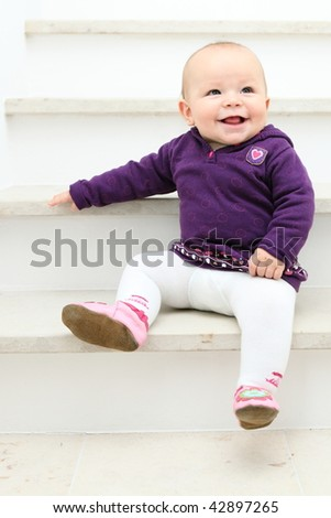 Baby girl smiling in very cute dress sitting on stairs - stock photo
