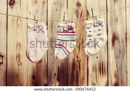 Baby girl socks on the clothesline. Vintage filter. - stock photo