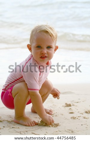 baby girl squatting down on a beach