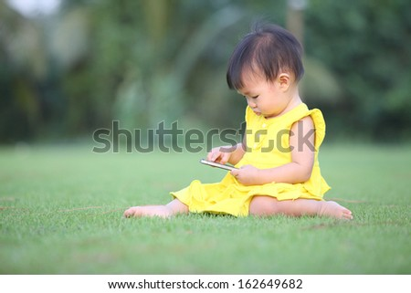 baby girl touch screen her smartphone on lawn - stock photo