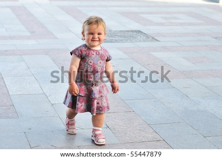 baby girl walking  by the street her first steps