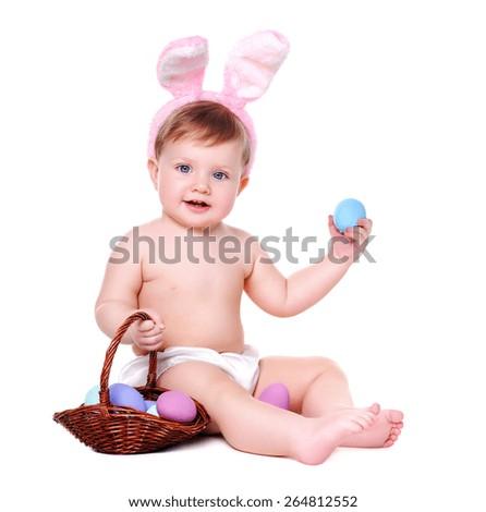 baby girl wearing bunny ears holding easter eggs - stock photo