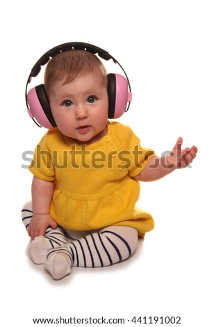 baby girl wearing pink ear defenders cutout - stock photo