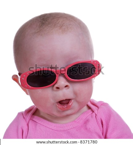 Baby girl wearing sunglasses with a cute expression - stock photo