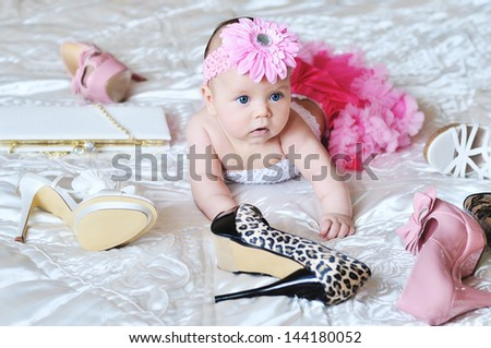 baby girl wearing tutu laying on the bed with high heels shoes and bags - stock photo