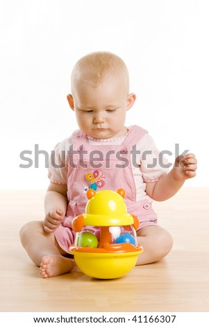 baby girl with a toy sitting on the floor