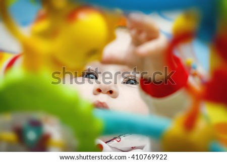 Baby girl with amazing blue eyes playing with baby carousel toys with a serious expression - stock photo