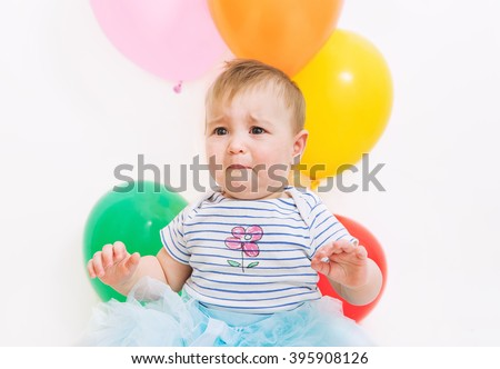 Baby girl with balloons crying - stock photo