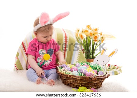 Baby girl with bunny ears and Easter basket with eggs  - stock photo