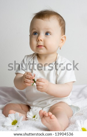 Baby girl with flowers sitting on a white blanket isolated on a white background, caucasian/white. - stock photo