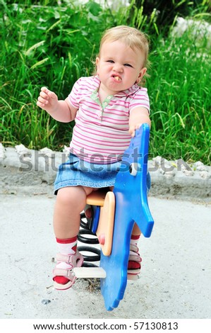 baby girl with funny face on spring swing