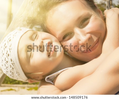 Baby girl with her mom in the sun outside. - stock photo