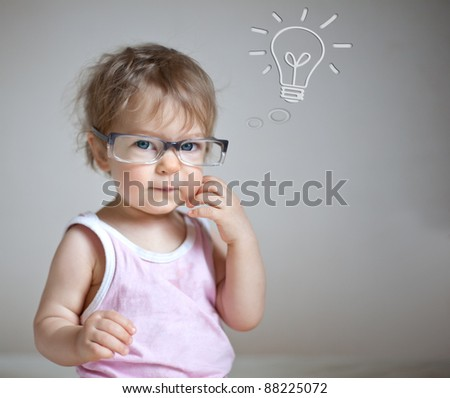 Baby girl with lightbulb against gray background