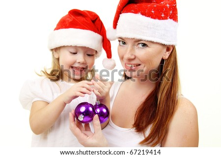 Baby girl with mother in Christmas hats - stock photo