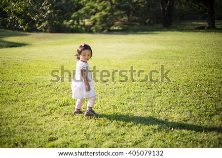 Baby girl with white dress walking on the grass field in the park - stock photo