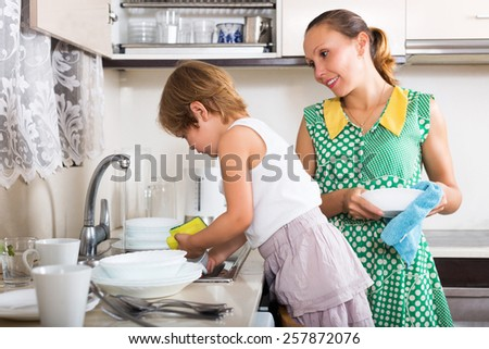 Baby girl  with woman washing plates in kitchen - stock photo