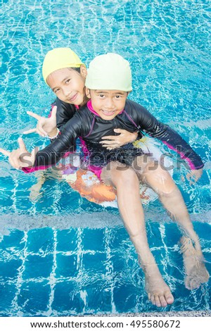 Baby Girls Asia enjoy Swimming in the pool. Happy summer holiday.