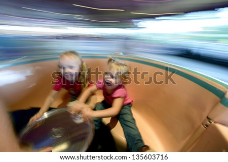 Baby girls on a roundabout. Shot with motion blur. - stock photo