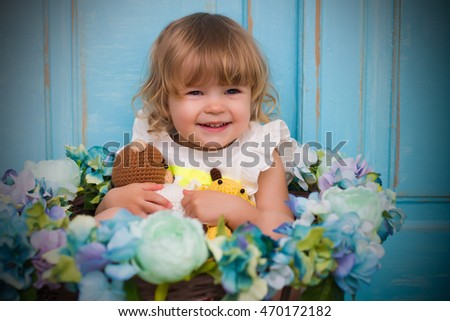 baby girls smiling on blue wooden background surrounding with flowers
