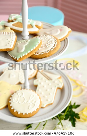 Baby glazed cookies in stand on decorated table