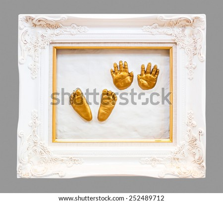 Baby hand and foot print in gypsum in a gold frame. - stock photo