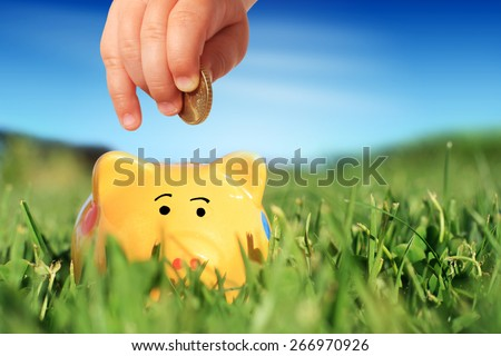 Baby hand and piggybank over nature background. - stock photo