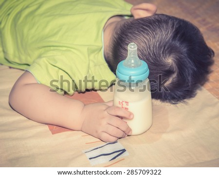 Baby hand hold milk bottle , vignette  - stock photo