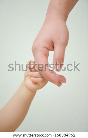 Baby hand holding finger  - stock photo