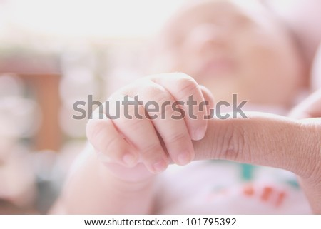 baby hand holding finger of mother