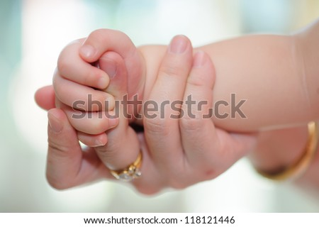 Baby hand holding mother hand