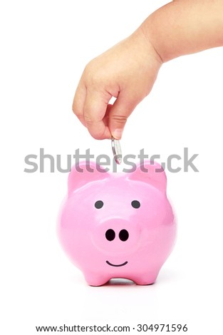 baby hand putting a silver coin into a pink piggybank