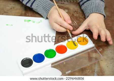 Baby hands and watercolors - stock photo