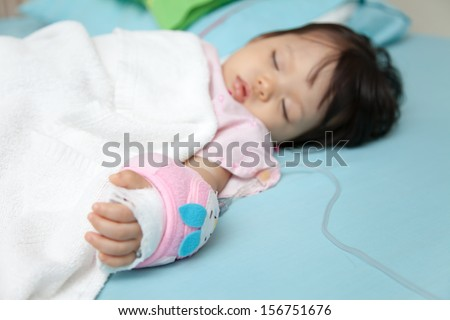 Baby have diarrhea and sleep on a bed in hospital with saline intravenous (iv) - stock photo